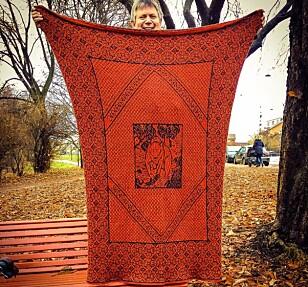 STORE TEPPER: En fordel ved å være mann som strikker er å kunne håndtere stort strikketøy, sier Kristian. Her med et egenprodusert teppe. FOTO: Privat / Facebook