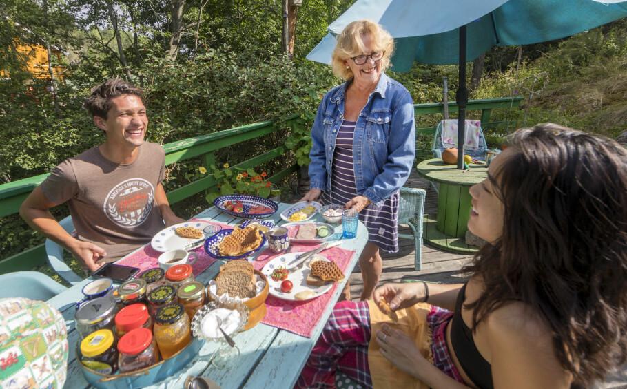 FROKOST: Bente Brenna (66) serverer frokost til alle gjestene. Her får Carl Oskar Thoen (28) og Amanda Nee (28) mat etter en natt i den rosa vanen. FOTO: Gorm Kallestad/NTB scanpix