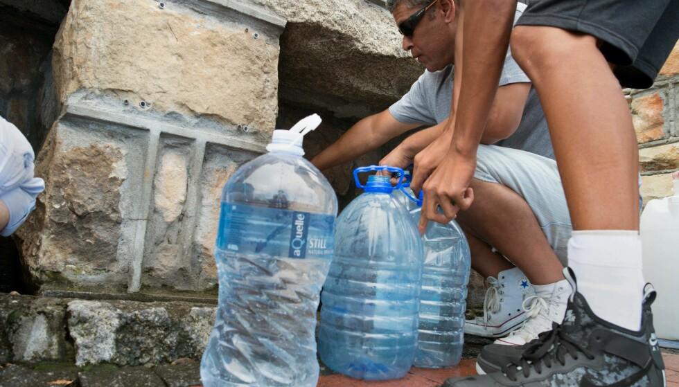 <strong>VANNMANGEL:</strong> Folk hentet vann fra kraner i gatene i Cape Town. Ordføreren sa den 18. januar i år at folks vannforbruk måtte kuttes ned til femti liter om dagen. Foto: Rodger Bosch/ AFP Photo