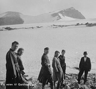 En gjeng på vei til toppen av Norges høyeste fjell - noen med penskjorten og hatten på. Foto: Nasjonalbiblioteket