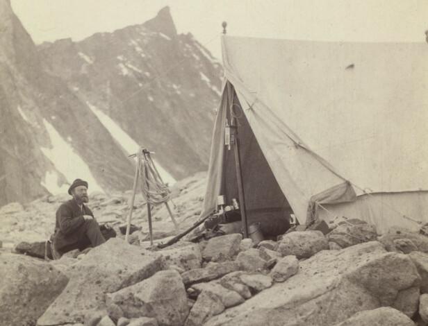 TELT: Torgeir Sulheim med hatt og frakk foran et telt på Store Skagastølstind, august 1887. Foto: Carl Christian Hall / Nasjonalbiblioteket