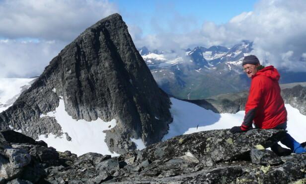 KLATRER: Forfatter av flere klatrebøker, Arne Larsen, på ryggen mellom Falketind og Stølsnostind i Vest-Jotunheimen, med toppen Stølsnostind i bakgrunnen. Foto: Privat