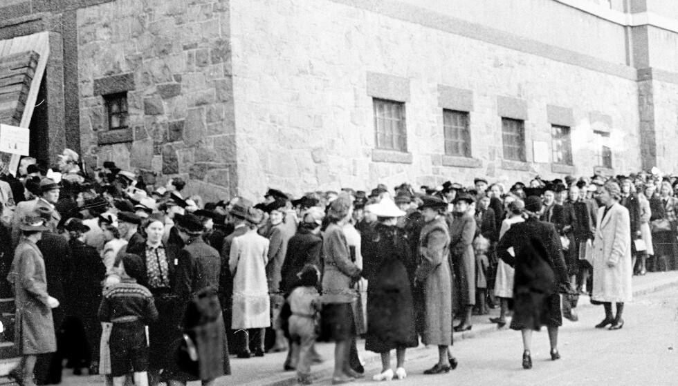 MATKORT: Folk står i kø utenfor Deichmanske bibliotek hvor rasjoneringskortene hentes. Foto: NTB Scanpix.