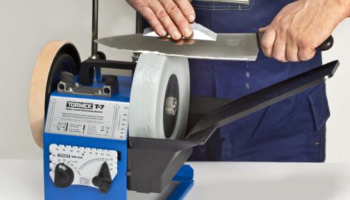 SLIPING: En maskin med roterende våtstein og anlegg koster en del penger, men gjør det enkelt å slipe kniver. Foto: Produsenten