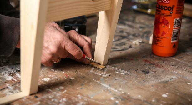 Stødig: Hvis ikke benken står støtt setter du kiler under de bena som er for korte. Deretter legger du en tynn kloss ved hvert ben og streker rundt. Til slutt sager du av bena etter streken. Foto: Øivind Lie-Jacobsen