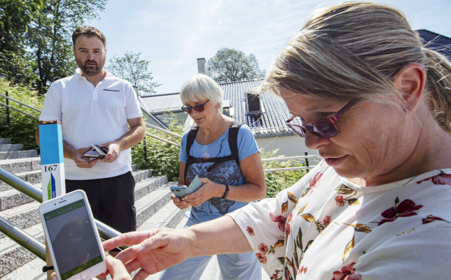 <strong>QR-kode:</strong> Stolpejaktens mobil-app gjør det enkelt å registrere stolpefunnene. Her er Liv Langberg (57) i ferd med å scanne inn QR-koden. Geir-Arne Eriksen (39) og Mona Ekeheien (63) venter på tur. FOTO: Geir Olsen/NTB scanpix.