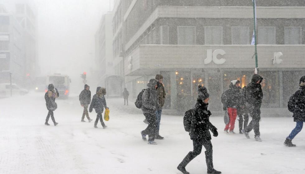 SNØSTORM I TROMSØ: Fotgjengere i Tromsø trosser snø og sterk vind i byen. Foto: Rune Stoltz Bertinussen / Scanpix.