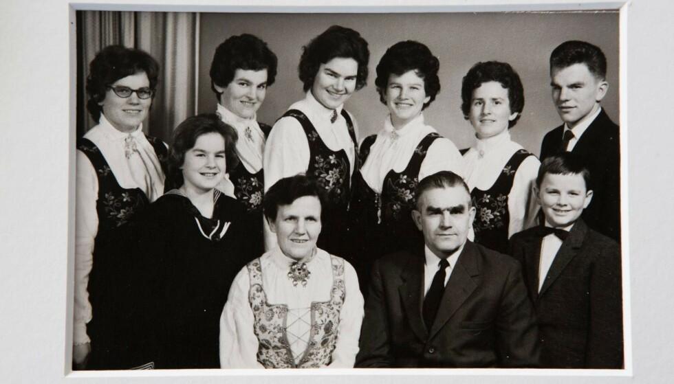 Alle sammen: Dette bildet ble tatt av hele familien i 1961. Bakerst fra venstre Kari, Ellen, Ingeborg, Oddbjørg, Ingrid og Per Olav. Fremst fra venstre Anne Marie, mor Inger, far Olav og Knut. Døtrene har Lundebydrakt, som tre av dem har brodert selv, mens Inger har brodert til Ingeborg og Kari. Inger har også sydd sin egen Solør/Odalsbunad. Foto: Privat
