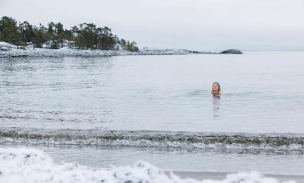 Til og med når hun må hakke hull i isen, bader Liina. Foto: Susanne Lindholm