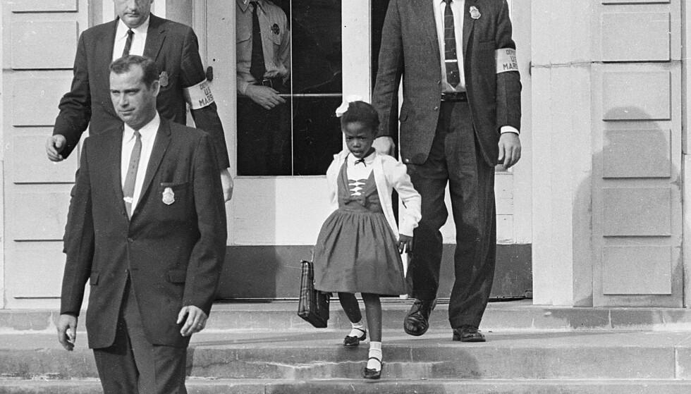 BILDE PÅ RASESKILLE: Ruby Bridges måtte følges av politimenn for å komme seg trygt forbi mobben ved William Frantz Elementary School i New Orleans i november 1960. Foto: AP NTB