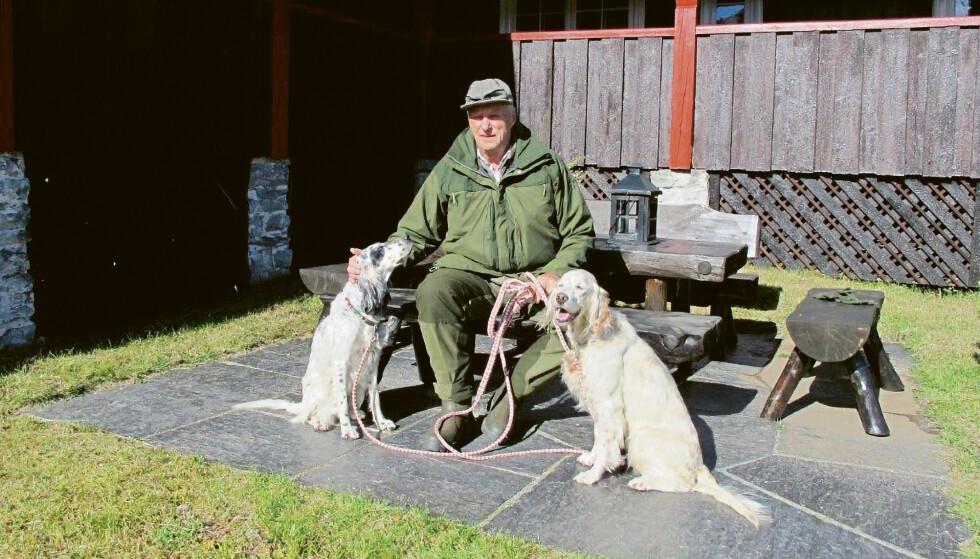 GLAD I NATUREN: Kong Harald med hund på hyttetunet. Foto: Dronning Sonja