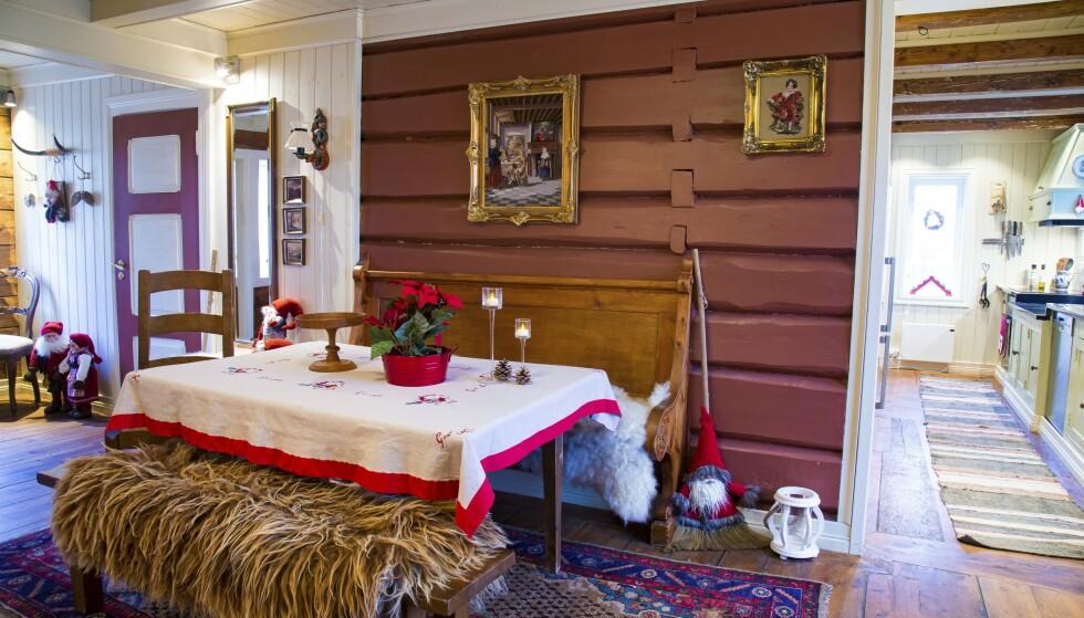 Koselig spiseplass: Benken som står inntil veggen ved spisebordet, stammer fra gården. På den andre benken ligger et saueskinn fra gårdens egen villsau. Veggen har fått tilbake sin opprinnelige farge. Bak skimtes kjøkkenet. Foto: Siv-Elin Nærø