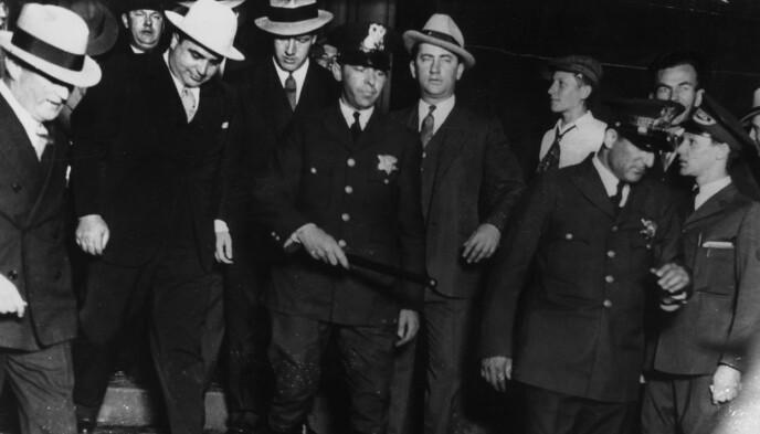DØMT FOR SKATTEUNNDRAGELSE: Av bildene som finnes av Al Capone, viser mange ham forlate et rettslokale. Her er han (nummer to med hvit hatt fra venstre) utenfor tinghuset i Chicago i 1931. Foto: Granger/REX/NTB