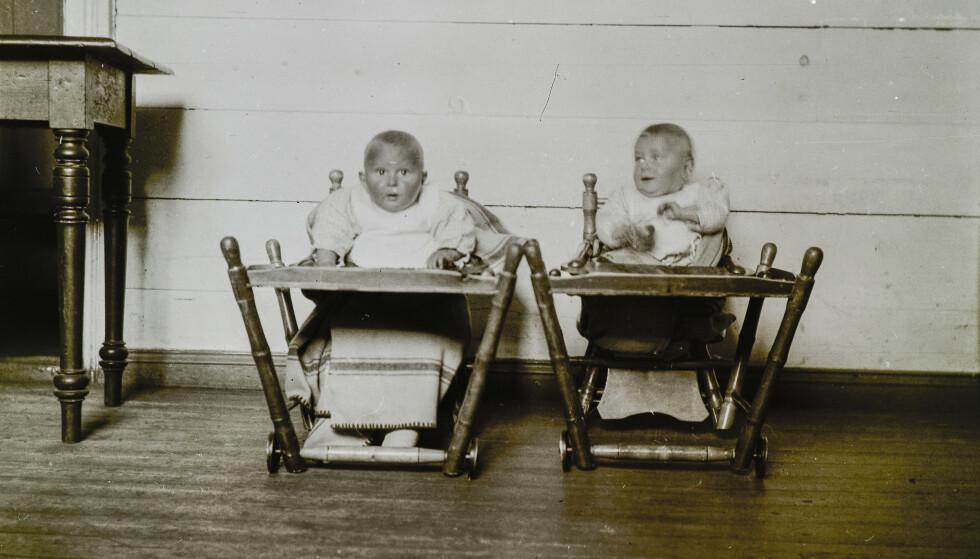 TATT FRA FORELDRENE: Norsk Misjon Blant Hjemløse forsøkte å få tak i romanibarn før de var fylt fire år. Jo tidligere de ble tatt fra foreldrene, jo mindre fikk de vite om egen familie og kultur. Portrettet av tvillingpar i hver sin barnestol ble tatt på Askviknes barnehjem mellom 1925 og1927. Foto: Riksarkivet