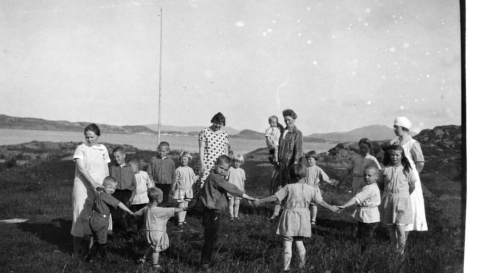 IDYLL? Barn og ansatte fotografert på Jacob Walnums barnehjem i Kopervik. Det ser ut som en lykkelig sommerdag, men mange av barna som misjonen tok fra foreldrene opplevde seksuelle overgrep og vannstell. Foto: Riksarkivet
