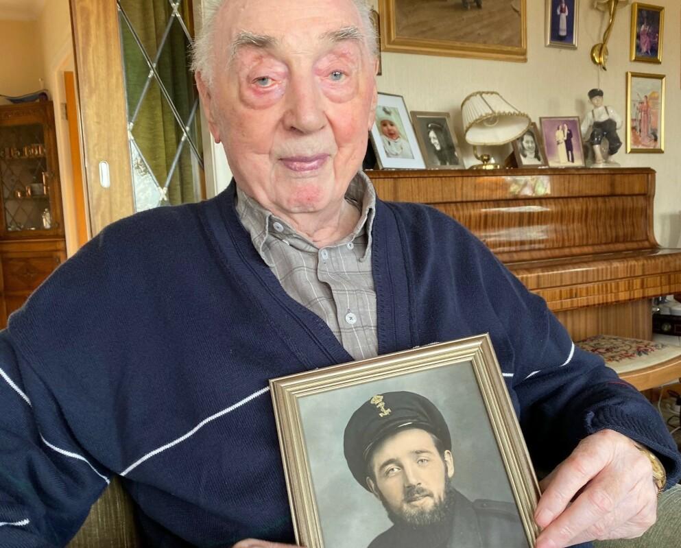 100-åring: Jakob Strandheim da han i fjor rundet 100 år. Bildet han holder er av en yngre utgave av seg selv. Foto: Privat