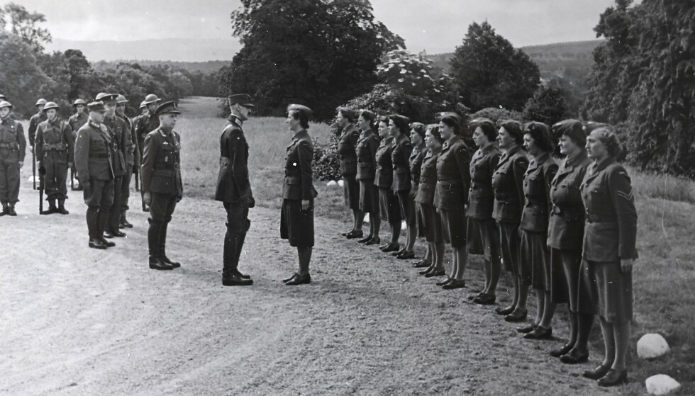 INSPEKSJON: Norsk Kvinnekorps ble opprettet på Kong Haakons 70-årsdag 3. august 1942. Her står fenrik Hanne Mossige i giv akt foran kongen når han inspiserer den kvinnelige troppen.