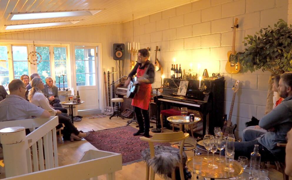 ÅPNER HJEMMET SITT: Bjørn Fjeldvær driver restaurant fra stua si hjemme i Trondheim, hvor han spiller, synger og serverer gode historier fra eget liv - i tillegg til å lage mat og servere. Her er det god stemning, løse kommentarer - og åpent for nye bekjentskaper. Foto: Kristin Sørdal
