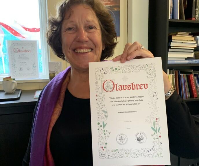Pilgrimsvert Jeannette Postma (72) viser frem Olavsbrevet som pilgrimmene mottar ved ankomst. Foto: Berit B. Njarga